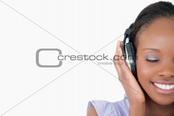 Close up of young woman enjoying music on white background