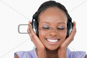Close up of young woman listening to music with headphones on white background