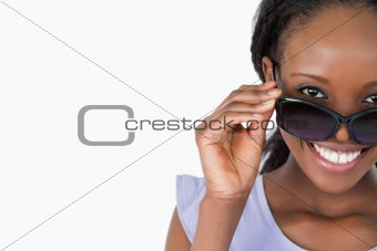 Close up of woman looking over her sunglasses on white background