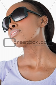 Close up of woman wearing her sunglasses on white background