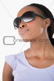 Close up of woman wearing her sunglasses against a white background