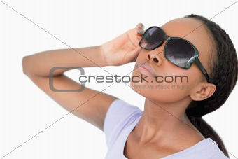 Close up of woman moving her sunglasses against a white background