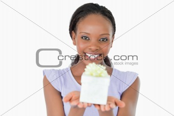 Close up of woman holding a present against a white background