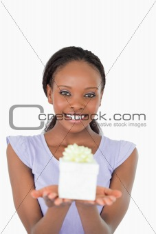 Close up of smiling woman holding a present against a white background