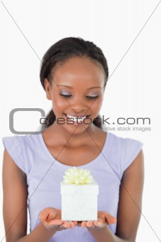 Close up of woman looking at a present against a white background