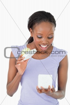Close up of woman being happy about a present against a white background