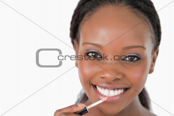 Close up of woman applying lip gloss against a white background