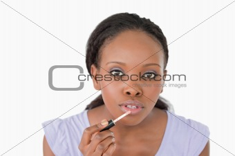 Close up of woman using lip gloss against a white background