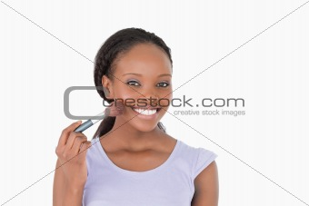 Close up of woman using make-up brush against a white background