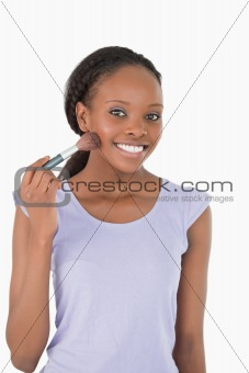 Close up of woman with make-up brush against a white background