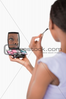 Close up of shadowing woman while applying make-up against a white background
