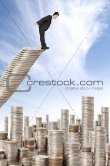 surprised businessman standing on the money stairs and watching many coin towers