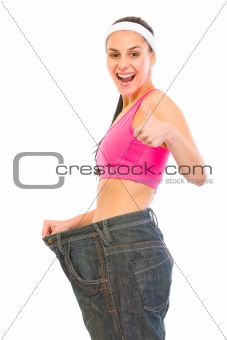 Slim female pulling oversized jeans. Weight loss concept