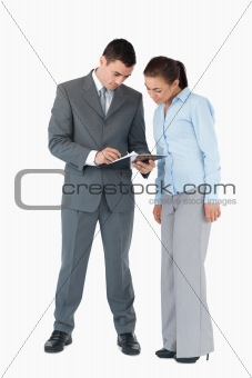 Business partner having a look at a clipboard against a white background