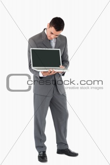 Businessman showing whats on his screen against a white background
