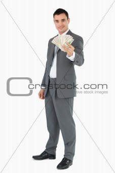 Smiling businessman presenting banknotes