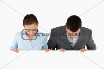 Business partners looking down at sign they are holding