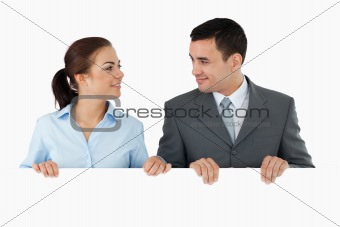 Business partners looking at each other while holding sign together