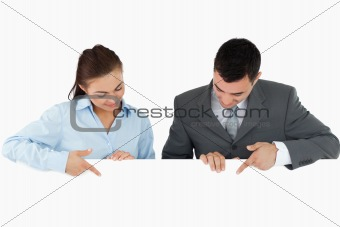 Business partners looking and pointing at sign they are holding