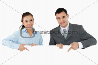Business partners pointing at sign they are holding