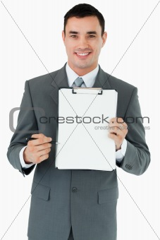 Smiling businessman pointing with pen at clipboard