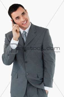Smiling businessman looking diagonally upwards while on the phone