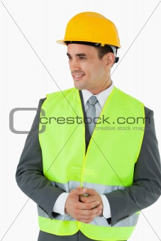 Smiling architect with hands folded looking to the side