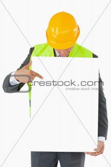 Architect looking and pointing on sign in his hands