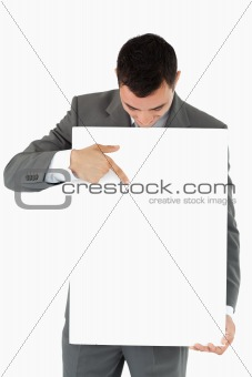 Businessman pointing at sign he is presenting