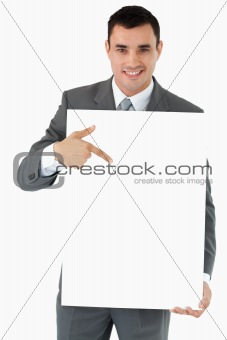 Smiling businessman pointing at the sign in his hands