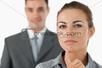 Close up of thinking businesswoman with colleague behind her