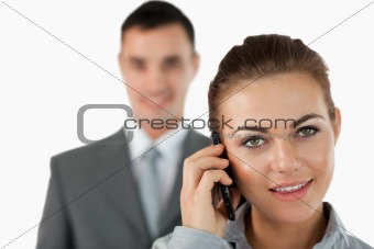 Close up of businesswoman on the phone with colleague behind her