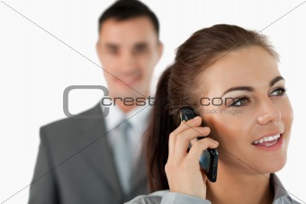 Close up of young businesswoman on the phone with colleague behind her