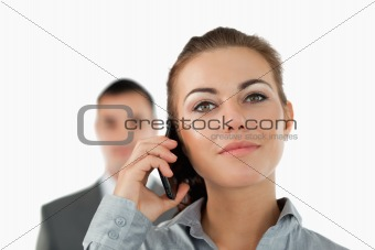 Close up of confident businesswoman on the phone with colleague behind her