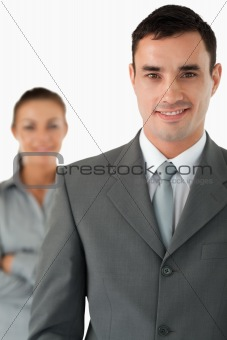Close up of smiling businessman with colleague behind him