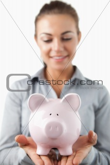 Close up of piggy bank being held by female bank assistant