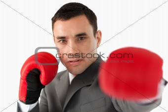 Close up of businessman with boxing gloves slamming
