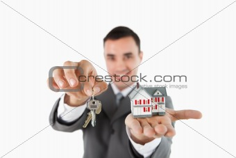 Close up of keys and miniature house being held by male estate agent