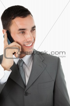 Close up of smiling businessman looking to the side while on the phone