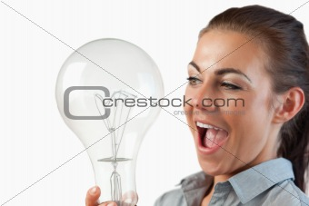 Close up of businesswoman being surprised by huge light bulb