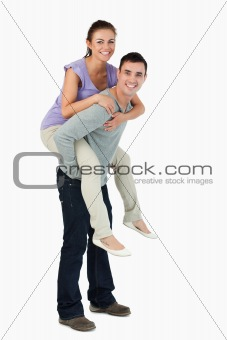 Young male carrying his girlfriend piggyback