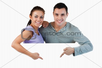 Young couple pointing at advertisement below them