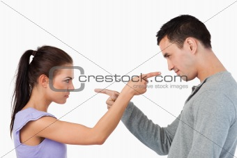Young couple pointing at each other
