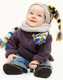 Cute baby boy in knitted handmade hat, scarf and bootees is sitt
