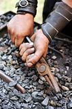 Detail of dirty hands holding pliers - blacksmith