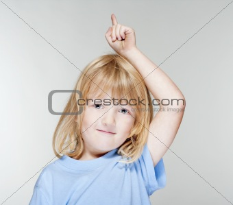 boy with long blond hair pointing up - isolated on gray
