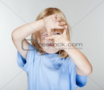 little boy with long blond hair looking through a finger frame - isolated on gray