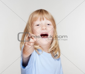 boy with long blond hair pointing towards the camera - isolated on gray