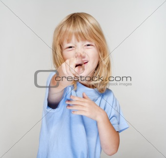 boy with long blond hair pointing towards the camera - focus on finger
