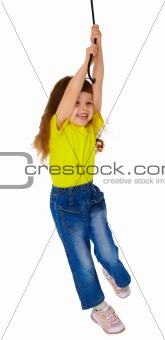 Little girl swinging on a rope